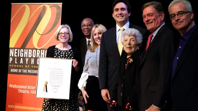 Photo of members of The Neighborhood Playhouse Board of directors assemble on the main stage with Executive Director Pamela Moller Kareman.  Pamela is holding an official proclamation from the City of New York.