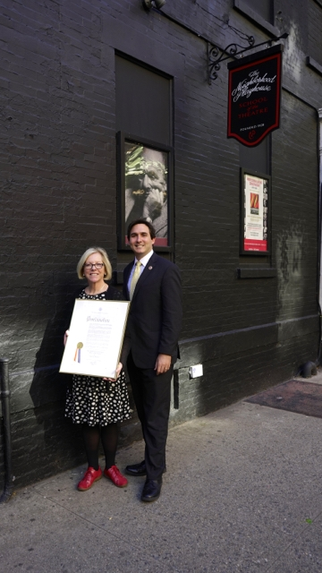 Photo of City Council member Ben Kallos, and Neighborhood Playhouse Executive Director Pamela Moller Kareman in front of the Bronze Plaque honoring The Playhouse.  Moller Kareman holds the framed proclamation.